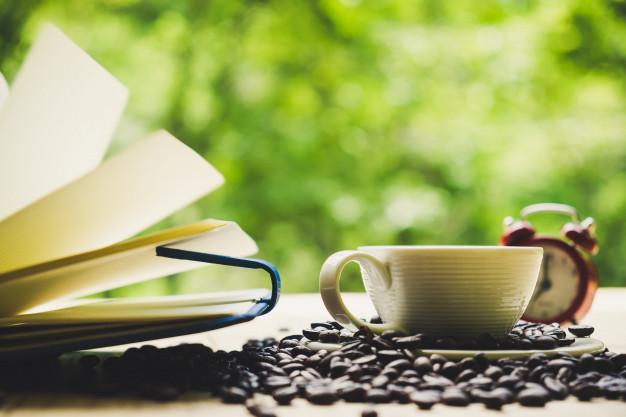 taza-de-cafe-portatil-blanco-granos-de-cafe-y-despertador-en-un-escritorio-de-tablon-de-madera-vista-superior_2379-306